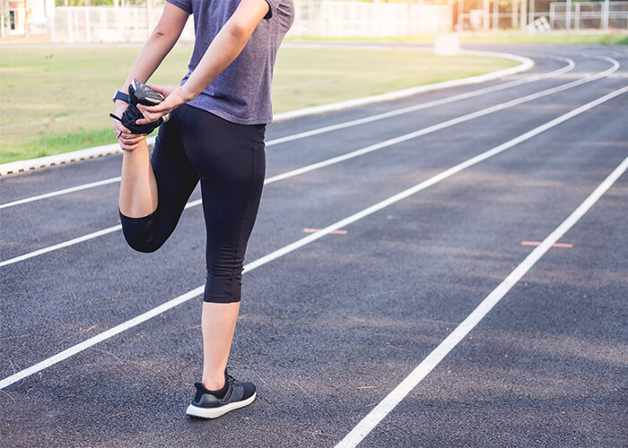 Woman on running track stretching her leg